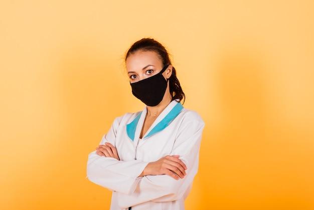 黄色の背景で隔離の美しいアフリカ系アメリカ人の医師または看護師の肖像画