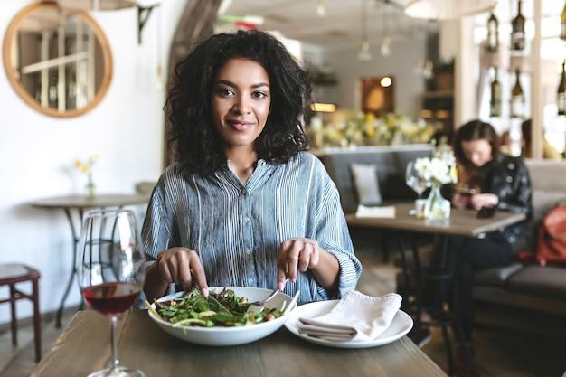 카페에 앉아 아름 다운 아프리카 계 미국인 여자의 초상화. 샐러드를 먹고 카페에서 레드 와인을 마시는 검은 곱슬 머리를 가진 어린 소녀