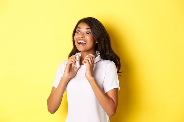 Портрет красивой афро-американской женщины, держащей наушники на шее и улыбающейся, изумленной глядя в левый верхний угол, стоящей на желтом фоне