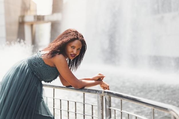 웃 고 일몰 동안 공원에서 멀리보고 아름 다운 아프리카 계 미국인 여자의 초상화. 웃는 흑인 여자의 야외 초상화입니다. 컬러 헤어 밴드와 함께 공원에서 웃 고 행복 명랑 소녀.