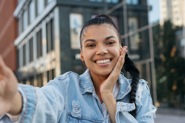 Портрет красивой афро-американской женщины, делающей селфи на открытом воздухе