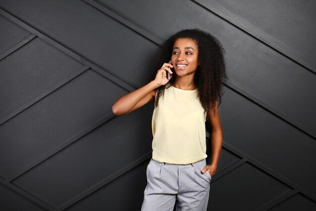 暗闇の中で携帯電話で話している美しいアフリカ系アメリカ人女性の肖像画