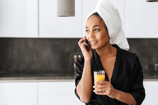 キッチンで携帯電話を使用して、バスローブを着ている美しいアフリカ系アメリカ人女性の肖像画