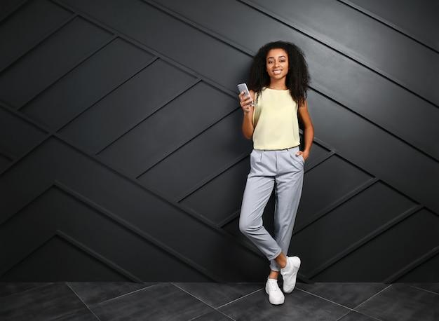 Портрет красивой афро-американской женщины с мобильным телефоном у темной стены