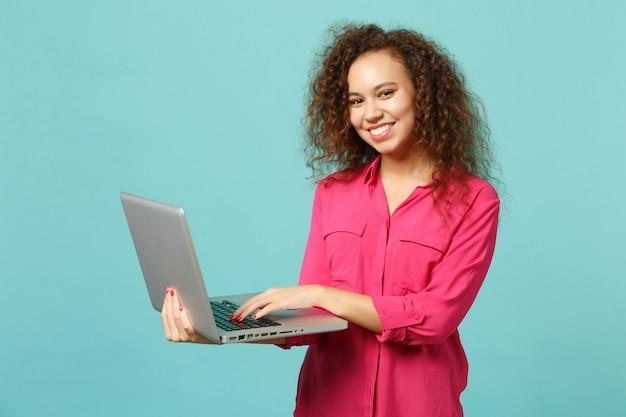 Портрет красивой африканской девушки в розовой повседневной одежде с помощью портативного компьютера, изолированного на синем бирюзовом стенном фоне в студии. люди искренние эмоции, концепция образа жизни. копируйте пространство для копирования.