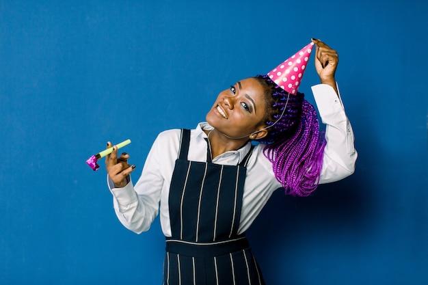 파티에서 쉬고 아름 다운 아프리카 여자의 초상화입니다. 푸른 공간에 생일 모자에 재미있는 아프리카 여자의 초상화. 축하와 파티.