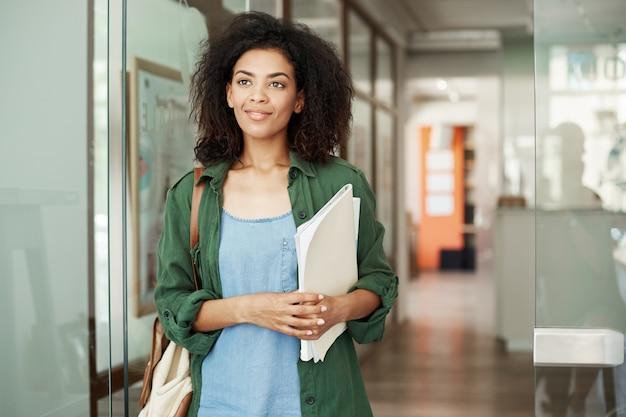 大学の廊下に立っている笑顔の持株本の側に立っている美しいアフリカ学生女性の肖像画。教育と学習の概念。