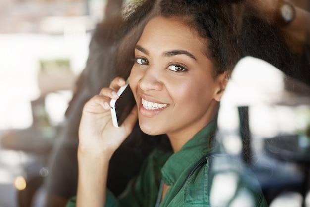 Портрет красивой африканской женщины за стеклом, улыбаясь, разговаривает по телефону
