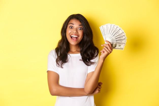 Портрет красивой афроамериканской девушки, улыбающейся счастливой и показывающей деньги, идущей по магазинам стоя