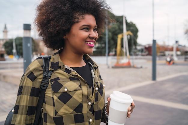 通りで屋外のコーヒーのカップを保持している美しいアフロアメリカンラテン女性の肖像画。都市のコンセプト。