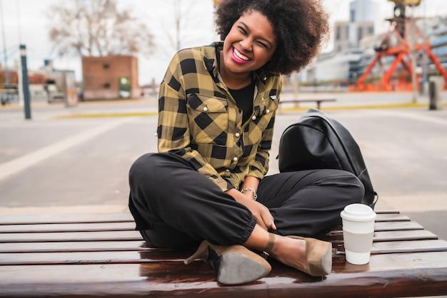 通りで屋外のコーヒーカップと座っている美しいアフロアメリカンラテン女性の肖像画。都市のコンセプト。