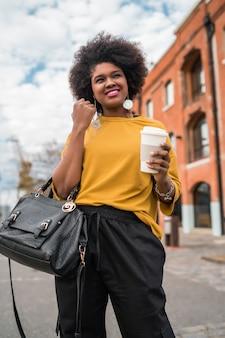 通りを歩いて、屋外で一杯のコーヒーを保持している美しいアフロアメリカンラテン女性の肖像画。都市のコンセプト。