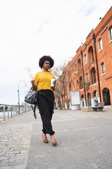 通りで屋外でコーヒーを歩いて保持している美しいアフリカ系アメリカ人女性の肖像画。アーバンコンセプト。