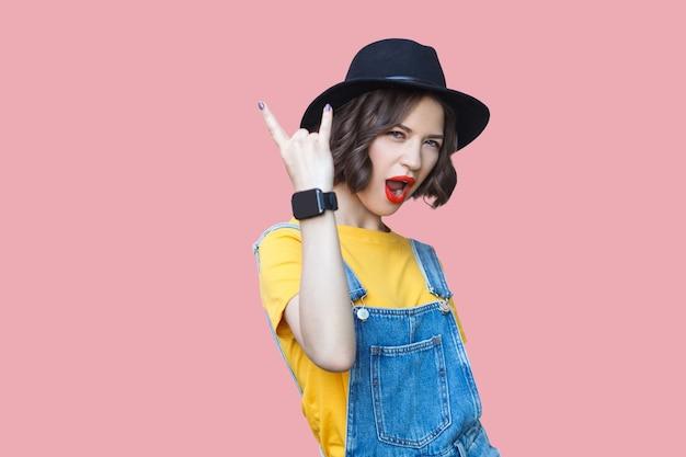 黄色のtシャツ、メイクアップの青いデニムのオーバーオール、岩の角で立って叫び、カメラを見ている黒い帽子の美しい驚いた若い女性の肖像画。ピンクの背景にスタジオ撮影。