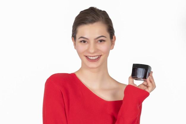Портрет красивой и смеющейся девушки в красном платье с антивозрастным кремом в руке