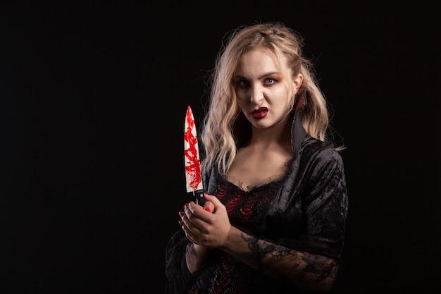 ハロウィーンのための美しく魅惑的な体の吸血鬼の女性の肖像画。ゴージャスな吸血鬼の女神。