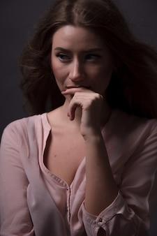 暗いスタジオで美しく官能的な白人女性の肖像画。