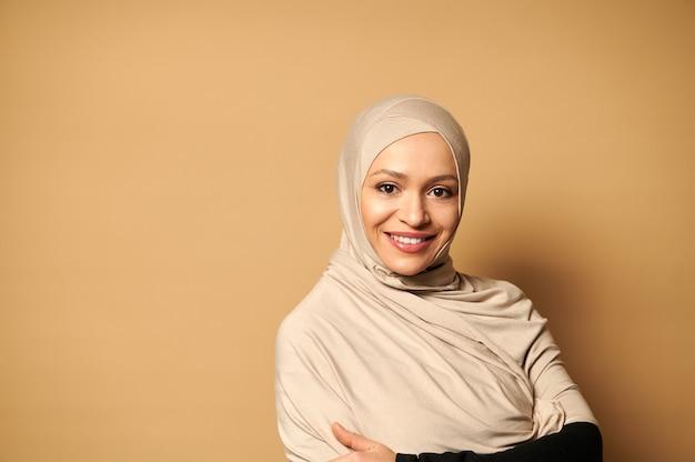 コピースペースとベージュの表面に歯を見せる笑顔でヒジャーブの笑顔で覆われた頭を持つ美しく成功したイスラム教徒のアラビア語の女性の肖像画