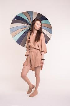 흰 벽에 우산 아래 서 아름 다운 아시아 갈색 머리 여성의 초상화