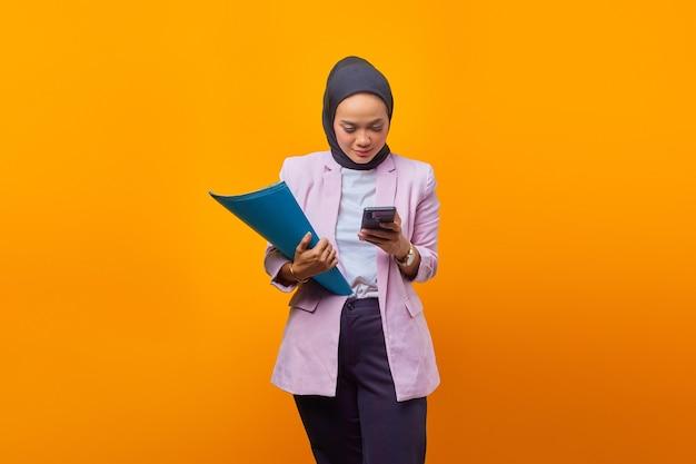 폴더를 들고 노란색 배경 위에 스마트폰을 사용하는 지루한 표정을 가진 아름다운 아시아 비즈니스 여성의 초상화