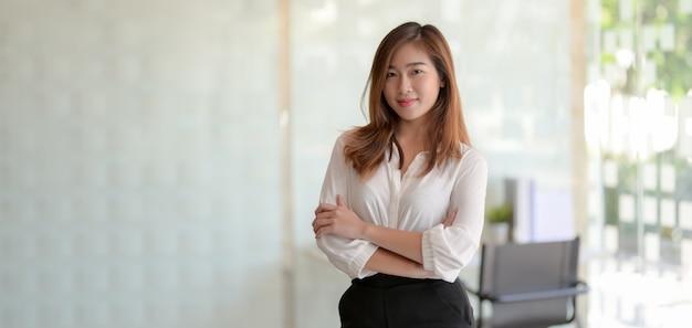 Портрет красивой азиатской коммерсантки стоя в комнате офиса и усмехаясь к камере