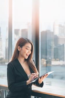 Портрет красивой азиатской коммерсантки с помощью цифрового планшета, стоя возле большого окна в современном офисе.
