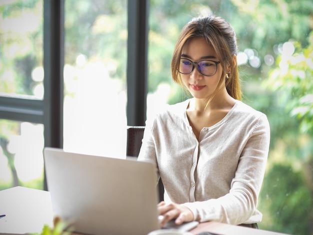 Портрет красивой азиатской бизнес-леди в очках, работающих на ноутбуке в офисе с размытым естественным фоном