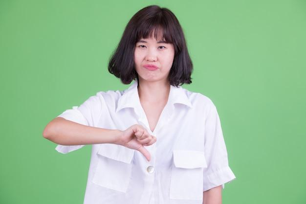 Портрет красивой азиатской бизнес-леди с короткими волосами на фоне цветного ключа или зеленой стены