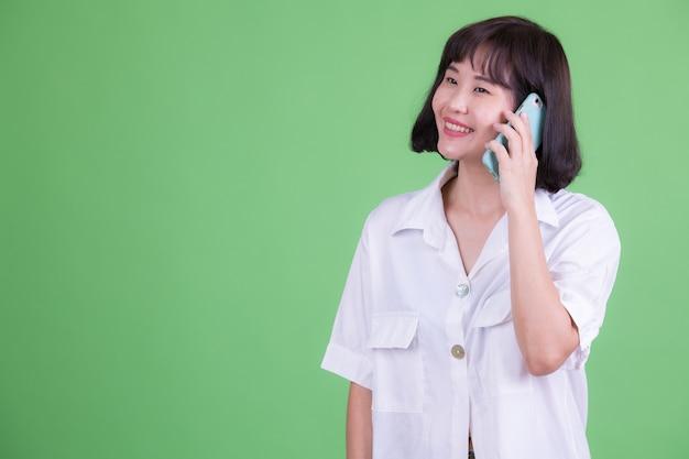 크로마 키 또는 녹색 벽에 짧은 머리를 가진 아름다운 아시아 사업가의 초상화