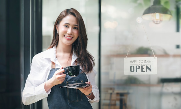 Портрет красивого азиатского предпринимателя, держащего чашку, стоящую в дверном проеме ее магазина с открытым знаком доски.