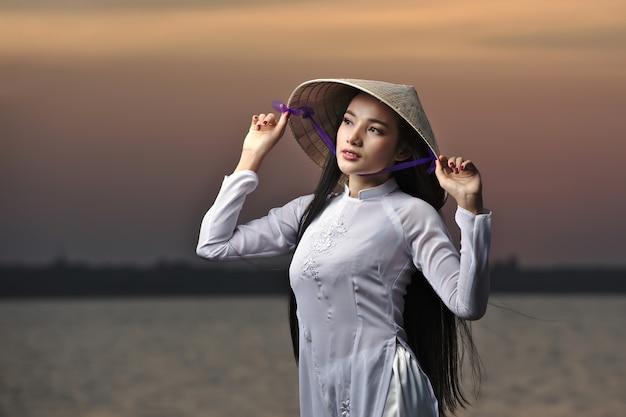 일몰 풍경에 ao dai 베트남 전통 드레스와 아름 다운 아시아 여자의 초상화.