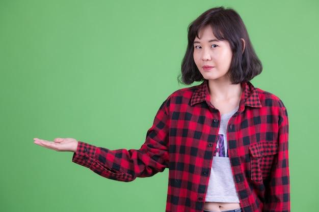 クロマキーまたは緑の壁に対して短い髪の美しいアジアの流行に敏感な女性の肖像画