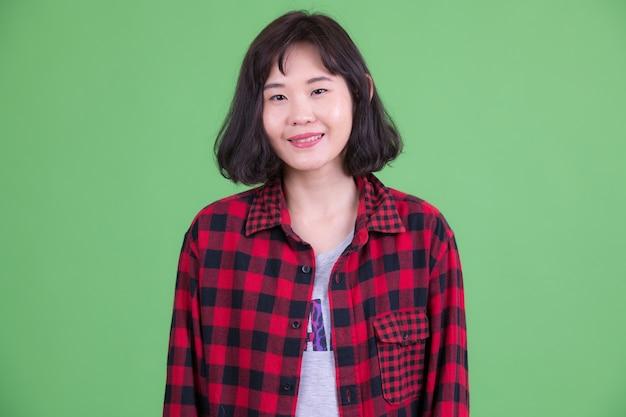 크로마 키 또는 녹색 벽에 짧은 머리를 가진 아름다운 아시아 힙 스터 여자의 초상화