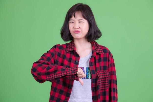 Портрет красивой азиатской хипстерской женщины с короткими волосами на фоне цветного ключа или зеленой стены