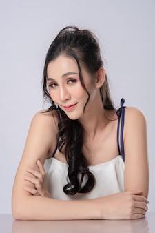 白のカメラを見て美しいアジアのモデルの長い髪の肖像画
