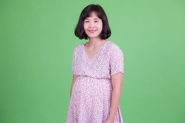 크로마 키 또는 녹색 벽에 짧은 머리를 가진 아름다운 아시아 임신 한 여자의 초상화