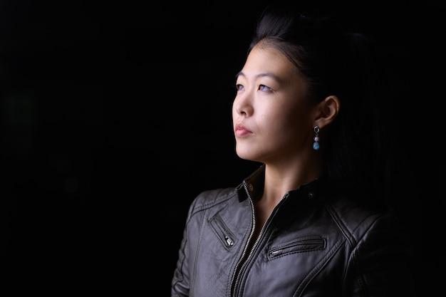 Портрет красивой азиатской мятежной женщины в кожаной куртке на улице на улице ночью