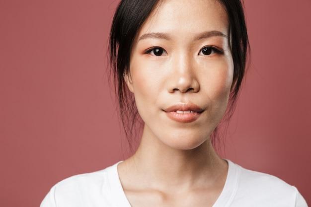 기본 옷을 입은 아름다운 아시아 여성의 초상화는 붉은 벽에 격리된 아름다운 시선으로 웃고 있다