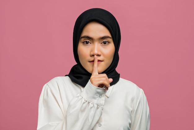 沈黙のために身振りで示すとカメラを見ている美しいアジアの女性の肖像画