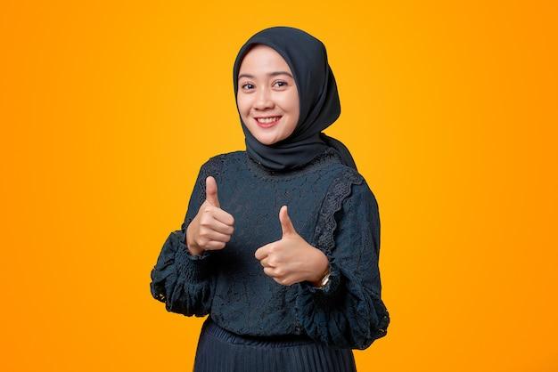 2 つの親指をあきらめる美しいアジアの女性の肖像画