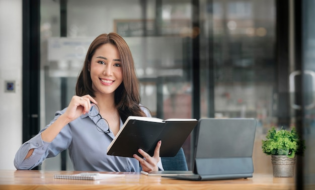 Портрет красивой азиатской женщины, держащей книгу и очки, улыбаясь и глядя на камеру, сидя за офисным столом.