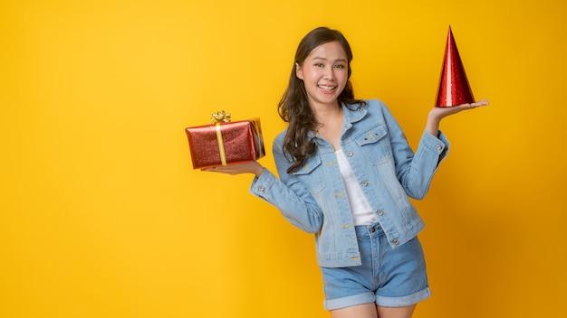 Портрет красивой азиатской женщины, держащей шляпу и подарочную коробку