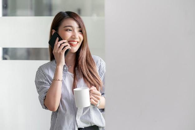 Портрет красивой азиатской женщины, держащей кружку и использующей смартфон со счастьем, стоя в офисе.