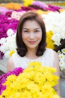 Портрет красивой азиатской женщины, держащей желтые цветы в руках с гордостью, владелец цветочного сада доволен продажей цветов хорошего качества.