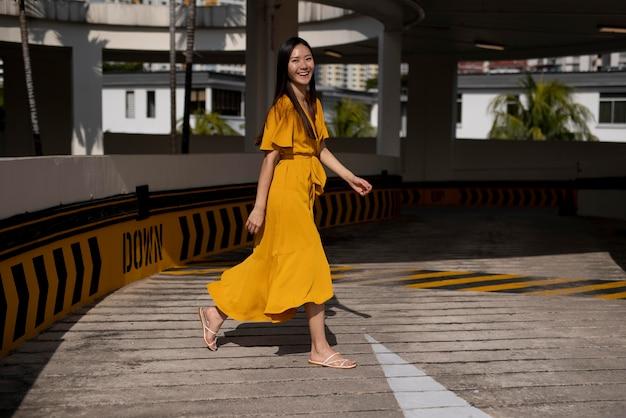 도시에서 야외에서 포즈를 취하는 노란 드레스를 입은 아름다운 아시아 여성의 초상화