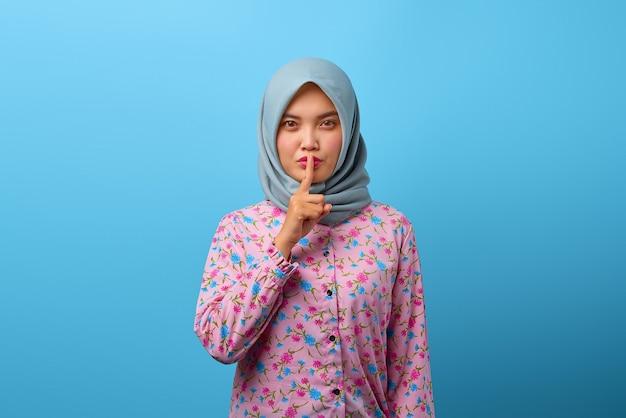 美しいアジアの女性の肖像画は指で沈黙のジェスチャーをします