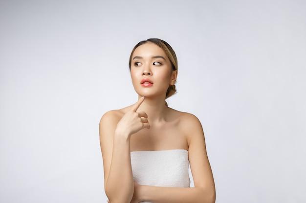 화장품의 아름 다운 아시아 여자 메이크업의 초상화, 여자 손 터치 뺨, 흰 벽에 고립 된 웰빙과 완벽 한 아름다움의 얼굴.