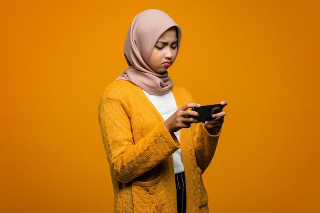 슬픈 표정으로 스마트 폰에서 비디오 게임을하는 아름다운 아시아 여자의 초상화