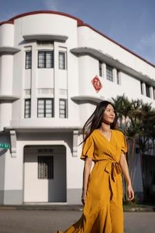 Портрет красивой азиатской женщины, позирующей в городе в желтом платье