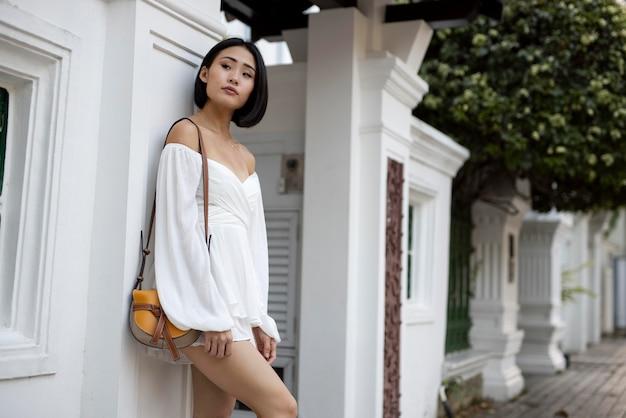 Портрет красивой азиатской женщины, позирующей на открытом воздухе в белом платье